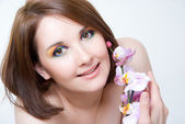 Girl's face and orchid — Stock Photo