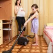 Stock Photo: Girl vacuums floor