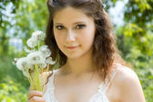 The young beautiful girl with dandelions — Stock Photo