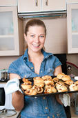 The woman with baking hot rolls — Stock Photo