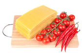 Lasagna pasta with tomato and pepper on cutting board — Stock Photo
