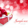 Little red gift with roses on festive background — Stock Photo