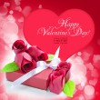 Little red gift with roses on background red heart — Stock Photo