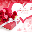 Little red gift with roses on background hearts — Stock Photo