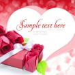 Little red gift with roses on background hearts — Stockfoto