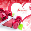 Little red gift with roses on background hearts — Stock Photo #8883953
