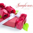 Little red gift with roses on white background — Stock Photo