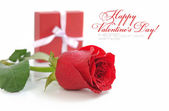Red rose with little gift are on a white background — Stock Photo