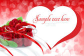 Heart-shaped box with red roses on a background a hearts — Stock Photo