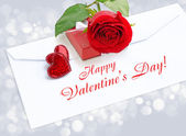 Two decorative hearts with a red rose and box by a gift on a pos — Stock Photo