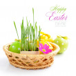 图库照片: Easter eggs and green sprouts are in a basket on a white background