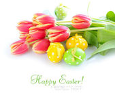 Easter eggs with tulips on white background — Stock Photo