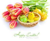 Samenstelling van tulip boeket met mandje met pasen eieren in de buurt van door op een witte achtergrond — Stockfoto