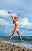 Cute young woman jumping with her arms in the air while at the beach — Stock Photo
