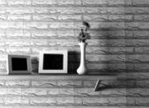 Florero de cerámica con flores y dos marcos en el estante — Foto de Stock
