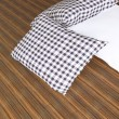 Black and white pillows on wooden parquet — Stock Photo #8956016