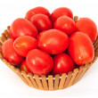 Fresh tomatoes on green branch in wicker basket isolated on whit - Stock Photo