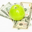 Green apple on dollar bills — Stock Photo