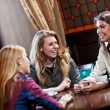 Pretty girl-friends talk and drink coffee in cafe house - Stock Photo