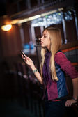 Young woman sending sms on smartphone in the interior of the bar — Stock Photo