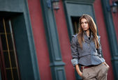 Young stylish woman against old building wall — Stock Photo