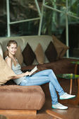 Woman sitting on sofa and reading book — Fotografia Stock