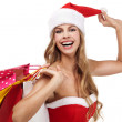 Portrait of a Christmas woman in santa costume holding a shoppin — Stock Photo