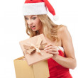 Happy Christmas woman holding gifts wearing Santa costume — Stock Photo