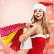 Charming woman in santa costume holding a shopping bags over red - Stock Photo