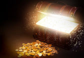 Old wooden treasure chest with strong glow from inside. — Stock Photo