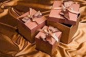 Three Christmas gift box on yellow satin background — Stock Photo
