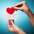 Woman's hand holding an envelope with a sign of the heart agains — Stock Photo