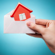 Woman's hand holding an envelope with a sign of the house agains — Stock Photo