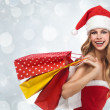 Charming woman in santa costume holding a shopping bags over win — Stock Photo