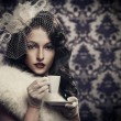 Young beautiful retro lady drinking coffee - Stok fotoğraf