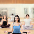 Portrait of healthy young woman practicing yoga on exercising ma - Stock Photo
