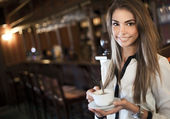 Young beautiful woman in a cafe with a cup of coffee — Stock Photo