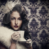 Young beautiful retro lady drinking coffee — Stockfoto