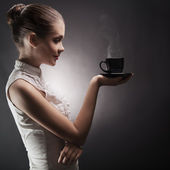 Attractive woman with an aromatic coffee in hands — Stock Photo