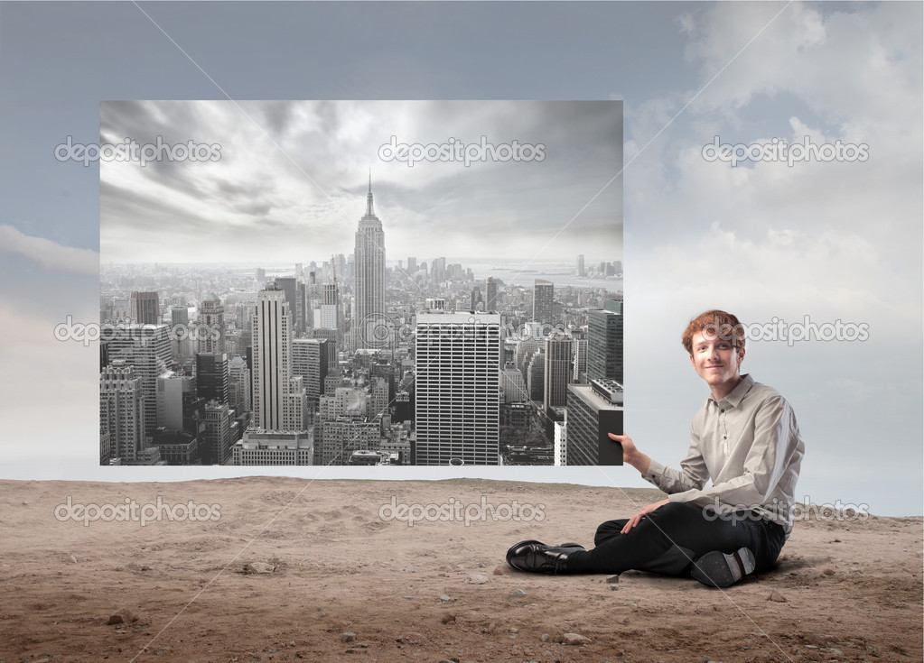Smiling young businessman holding a picture of an aerial view of a big city — Stock Photo #10167582