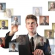 Stock Photo: Young businessman touching icons of different on a screen