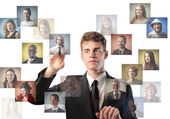 Young businessman touching icons of different on a screen — Stock Photo