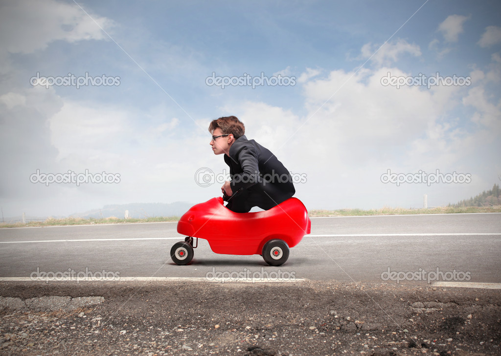 Young businessman driving a toy car on a country road — Stock Photo #10251701