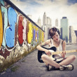 Beautiful young woman sitting on a city street and playing the electric guitar — Stockfoto