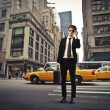 Isolated smiling young businessman on a city street — Foto Stock