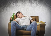 Young man sleeping on an armchair while holding a beer bottle and a bowl of chips — Stock Photo