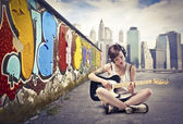Beautiful young woman sitting on a city street and playing the electric guitar — Stock Photo