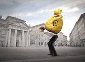 Young businessman carrying a money-bag on his shoulders on a town square — Stock Photo