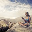 Photo: Smiling african woman sitting on a rock and using a tablet pc
