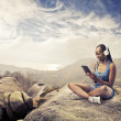 Foto Stock: Smiling african woman sitting on a rock and using a tablet pc